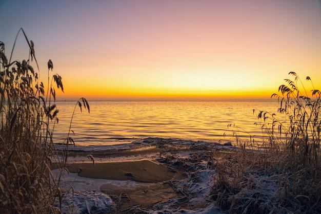 De eerste stralen van de zon over het ladogameer in de ochtend in de winter.