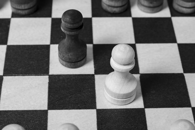De eerste zet bij het schaken werd gedaan door pionnen die elkaar tegenkwamen. schaakspel start, close-up, selectieve focus zwart en wit