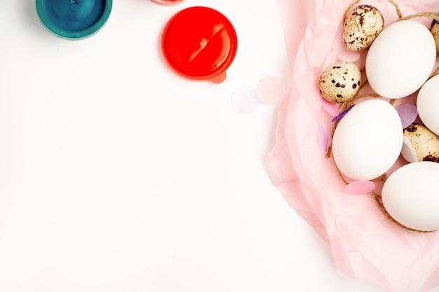 De eieren van de kip en van de kwartels nestelen en schilderen op wit achtergrond gelukkig pasen ambachtconcept
