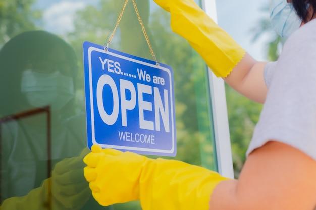 De eigenaar van de winkel hangt een bordje voor de opening van een zaak voor de deur.