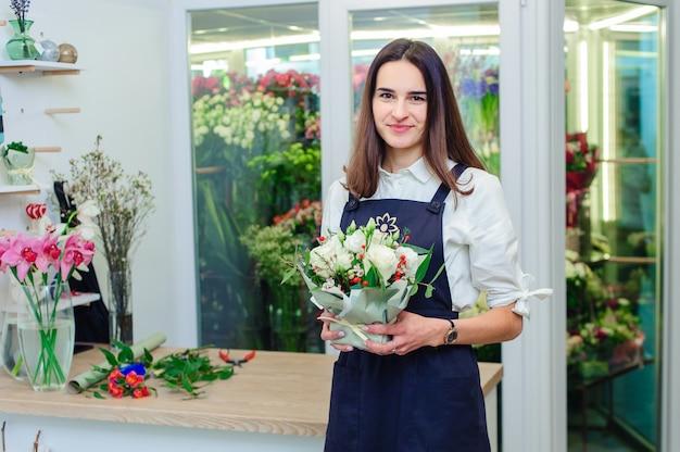 De eigenaar van een bloemenwinkel maakt een boeket met witte rozen
