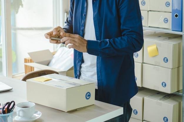 De eigenaar van een e-commercebedrijf neemt een foto van goederen die via een sociaal netwerk naar de klant worden gestuurd.