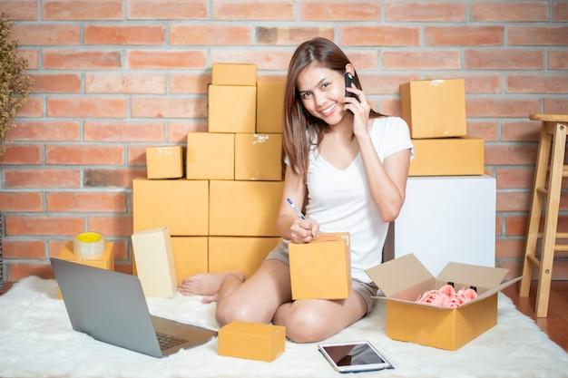 De eigenaar van het vrouwelijke ondernemer mkb-bedrijf controleert de bestelling met telefoon, laptop en verpakkingsdoos om haar klant te sturen