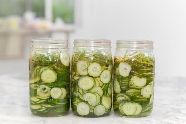 De eigengemaakte groenten in het zuur van plakkomkommers in een kruik op marmeren lijst.