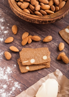 De eigengemaakte koekjes van het amandelkoekje met ruwe amandelen en boter op houten achtergrond