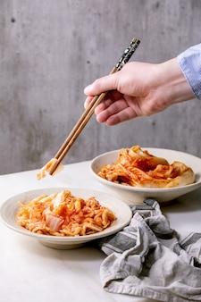 De eigengemaakte koreaanse traditionele gefermenteerde kool van voorgerechtkimchi die in ceramische plaat over witte marmeren muur wordt gediend. eetstokjes in handen van de mens.
