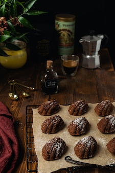 De eigengemaakte madeleine koekjes van de bakkerijchocolade bij het koelen van rek met ingrediënten en werktuigen op rustieke houten