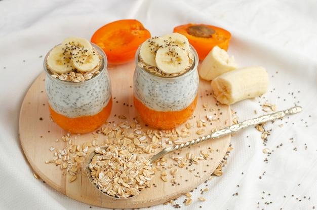 De eigengemaakte pudding van het chiazaad met banaan, gebroken verse abrikozen en havermaaltijden op houten raad met exemplaarruimte.