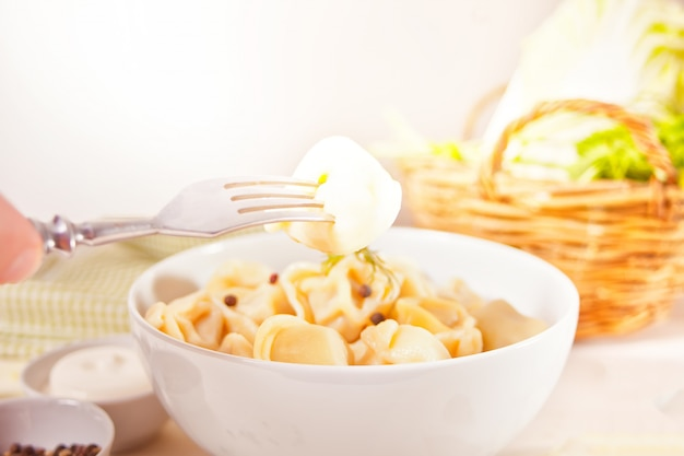 De eigengemaakte russische de bollen italiaanse ravioli van het pelmenivlees in de witte kom.