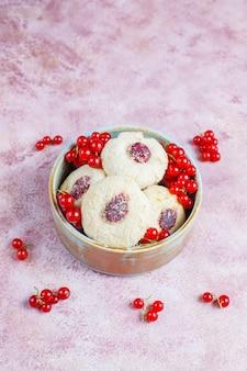 De eigengemaakte rustieke vullende koekjes van de rode aalbesjam met kokosnoot
