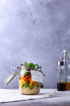De eigengemaakte salade in glaskruik met quinoa en groenten met etiketlunchtijd geen plastiek en haalt concept weg