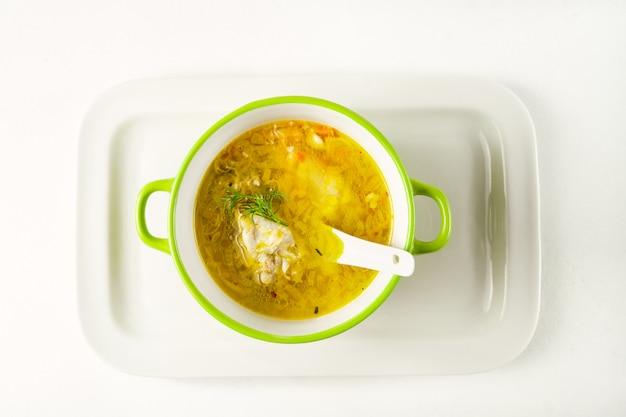 De eigengemaakte soep van de deegwarenkip diende in een kom op een wit dienblad
