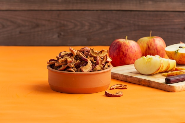 De eigengemaakte spaanders van de gedroogd fruitappel op een oranje achtergrond