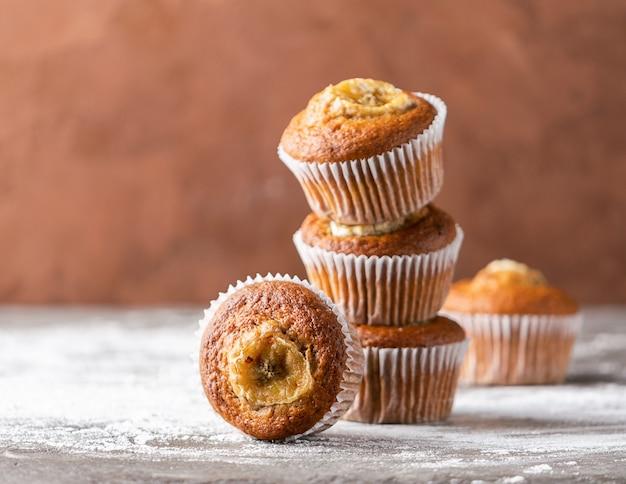 De eigengemaakte stapel van banaanmuffins op een bruine achtergrond. gezond vegan dessert.