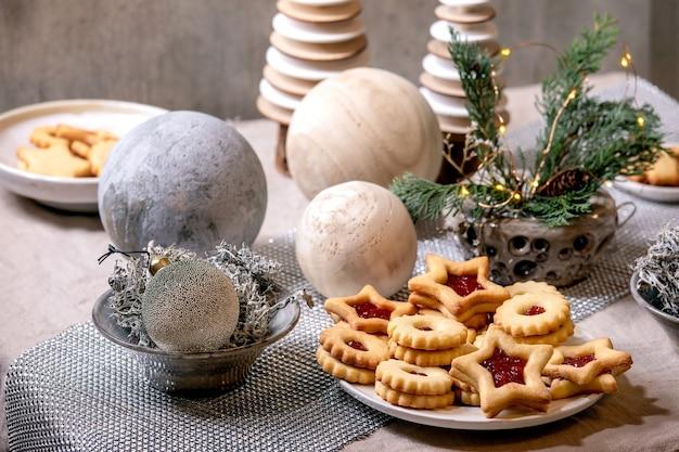 De eigengemaakte traditionele koekjes van de zandkoekkoekjes van kerstmislinz met rode jam op plaat. trend houten eco-vriendelijke kerstversieringen op linnen tafelkleed. vakantie tafel instelling.
