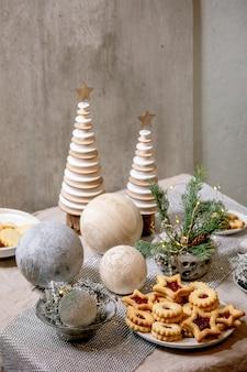 De eigengemaakte traditionele koekjes van de zandkoekkoekjes van kerstmislinz met rode jam op plaat