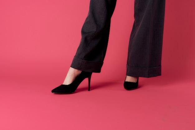 De elegante benen zwarte schoenen van vrouwen mode roze achtergrond