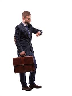 De elegante man in een pak met een aktetas die op zijn horloge kijkt