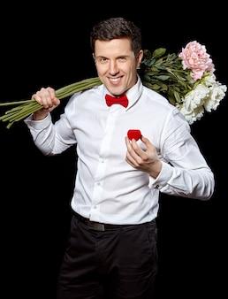 De elegante man met een ring en bloemen