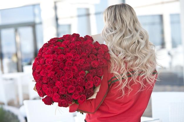 De elegante mooie blondevrouw draagt groene manierkleding in koffieholding met groot boeket van 101 rode rozen.