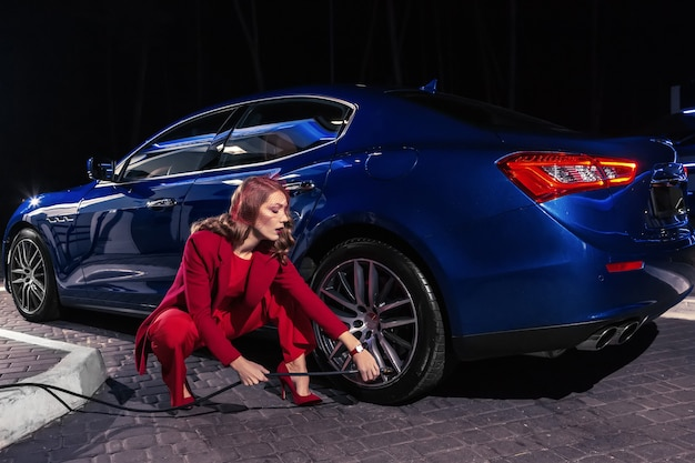 De elegante mooie vrouw vult lucht in een autoband om de druk op de autoband te verhogen.