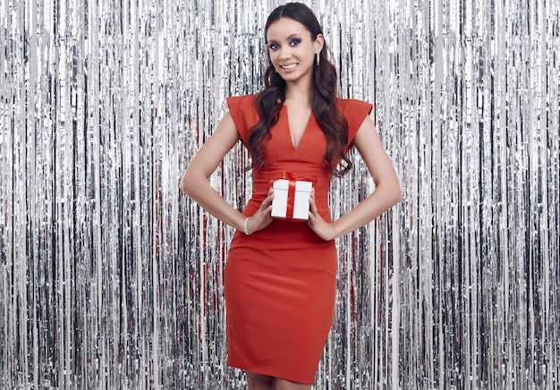 De elegante spaanse donkerbruine vrouw in luxueuze rode kleding houdt een giftdoos
