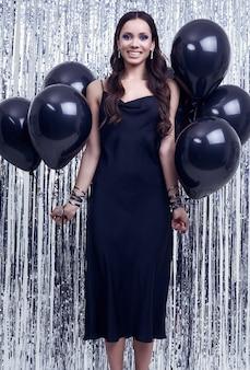 De elegante spaanse donkerbruine vrouw in luxueuze zwarte kleding houdt ballons