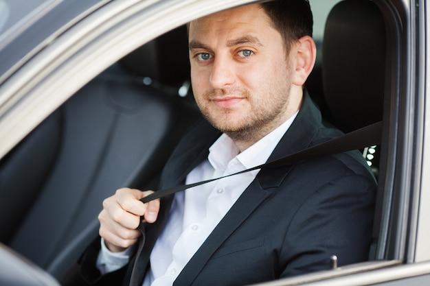 De elegante zakenman kleedde zich in het kostuum dat de veilige riem vastmaakt alvorens zijn auto te drijven