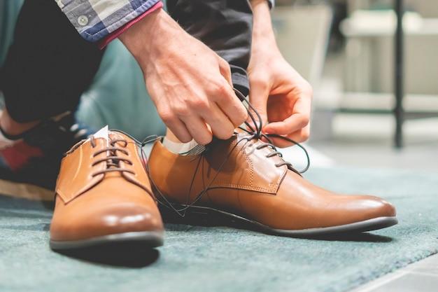 De elegante zakenman probeert op nieuwe bruine klassieke schoenen