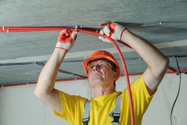 De elektricien bevestigt een elektrische golfbuis aan het plafond