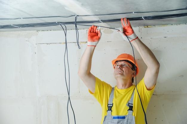 De elektricien die elektrische kabels aan het plafond bevestigt