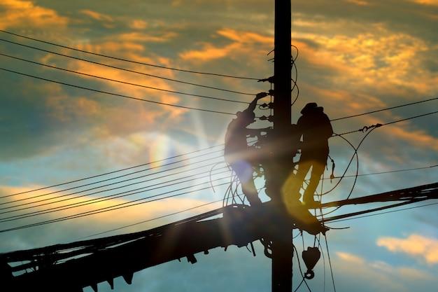 De elektricien die van silhouetmensen hoog op hemel werken.
