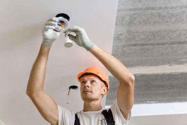 De elektricien installeert led-spots aan het plafond.