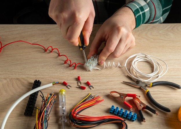 De elektricien schroeft de draad met een schroevendraaier op de connector