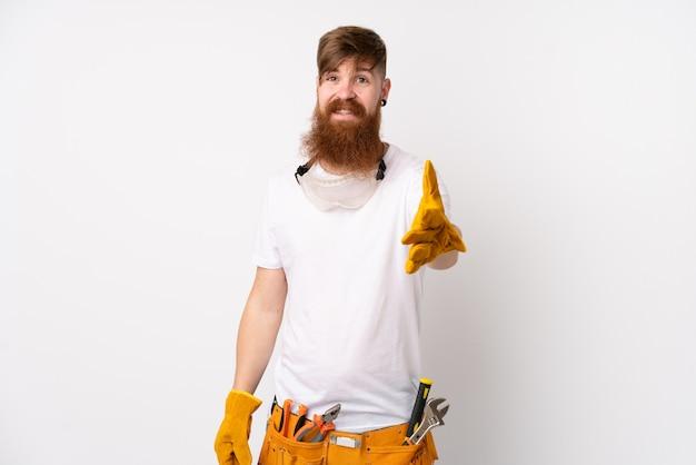 De elektricienmens van de roodharige met lange baard over wit muurhandenschudden na veel