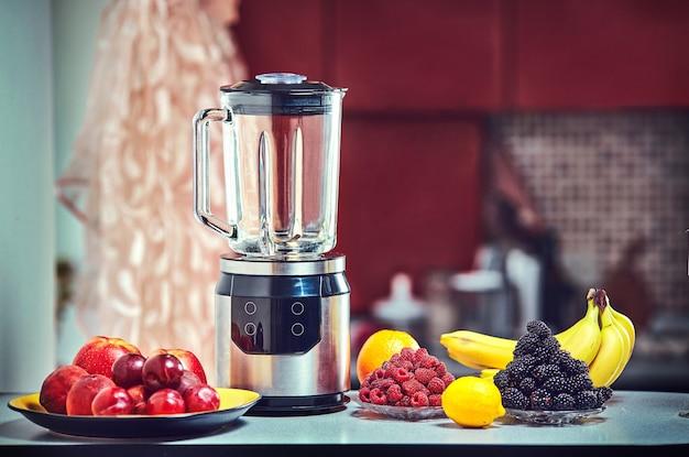 De elektrische blender voor het maken van vruchtensap of smoothie op houten keukentafel.