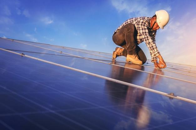 De elektrische en instrumenttechnicus heeft ontspannen terwijl hij de sleutel gebruikt om het elektrische systeem op het zonnepaneelveld te onderhouden