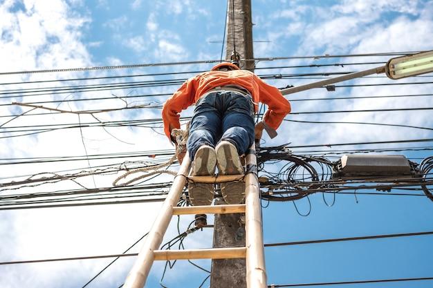 De elektrische lijnwachterarbeider beklimt een bamboeladder om draad te herstellen