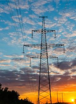 De elektrische pyloon van de silhouettenhoogspanning op zonsondergangachtergrond.