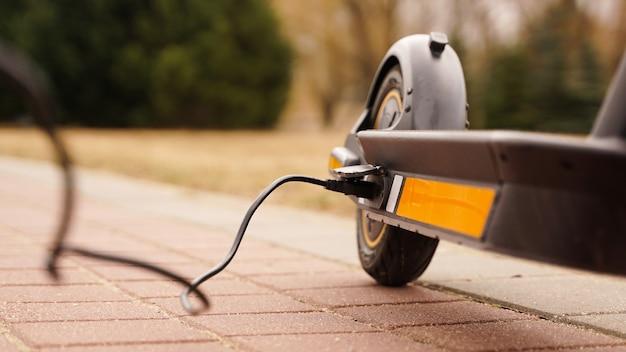 De elektrische scooter laadt buiten op, de draad loopt in de camera
