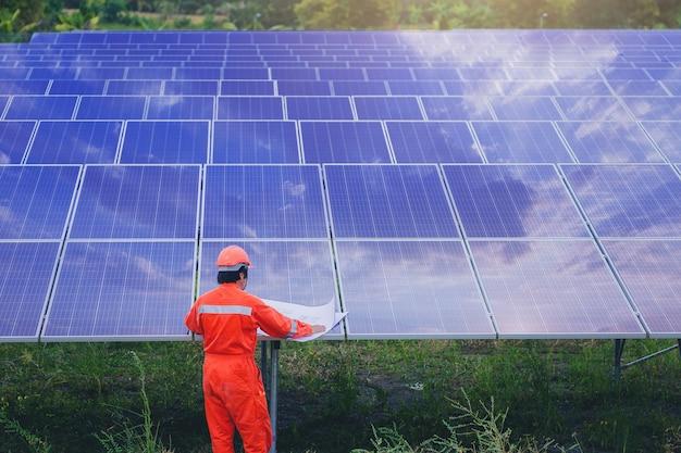 De elektro en instrument technicus gebruiken blauwdruk om elektrisch systeem bij zonnepaneelgebied te plannen en te handhaven