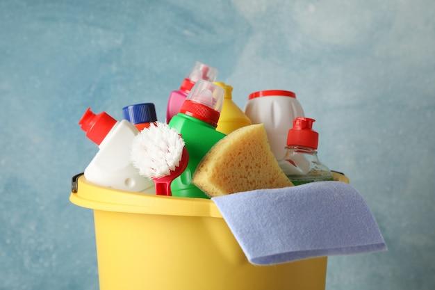 De emmer met detergens en schoonmakende levering op blauwe achtergrond, sluit omhoog