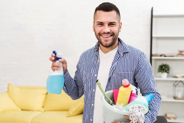 De emmer van de de mensenholding van smiley met schoonmakende producten