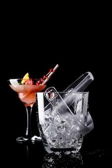 De emmer van het glasijs en de cocktail van margarita in glas op zwarte wordt geïsoleerd die