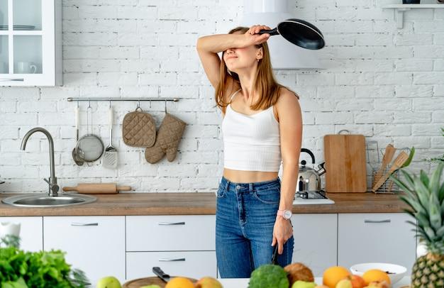De emotionele en mooie vrouw bereidt eten in een koekenpan in de keuken