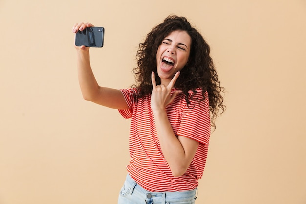 De emotionele jonge krullende vrouw maakt selfie die rotsgebaar toont.