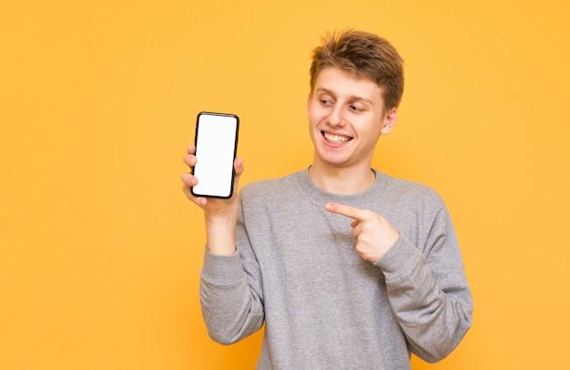 De emotionele jonge mens die zich op geel bevindt houdt een smartphone in zijn handen en bekijkt het witte scherm, dat een vinger toont