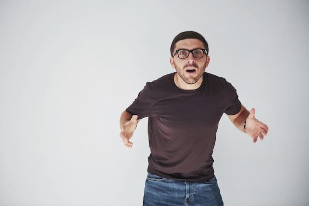 De emotionele persoon in vrijetijdskleding en met een bril ziet eruit alsof de onherstelbare fout is gemaakt