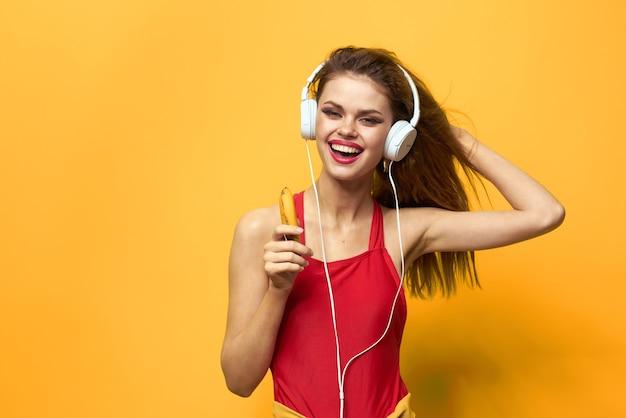 De emotionele vrouw die hoofdtelefoons draagt luistert naar de gele achtergrond van de muziekclose-up