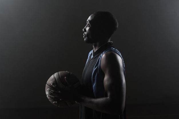 De ene kant van een basketbalspeler met een basketbal